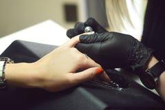 紫胶撤除 大师做修指甲 在美容院的松弛天 修指甲师大师在妇女` s手做修指甲 免版税图库摄影