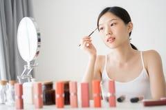 由眼眉刷子的年轻亚洲女性构成秀丽 免版税库存图片