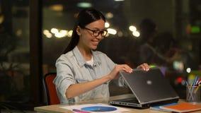疲倦的妇女完成在膝上型计算机的工作,满意对有生产力的平时 股票录像