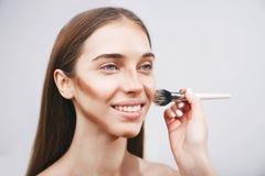 申请在妇女粉末的专业化妆师 库存照片
