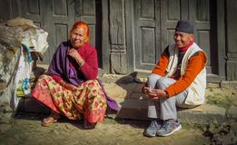 男人和妇女坐遏制观看的人民路过,巴克塔普尔,尼泊尔 免版税库存图片