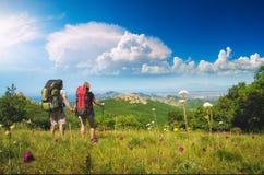 男人和妇女徒步旅行者在山谷 免版税库存图片