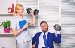 男人和妇女提高重的哑铃 强的强有力的经营战略 好工作概念 上司商人和办公室 免版税库存照片