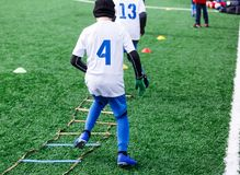 男孩以白色和蓝色橄榄球体育形式在绿色领域做锻炼 孩子的橄榄球,活跃生活方式 培训 库存照片