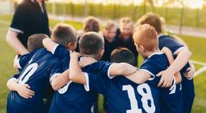 男孩体育队杂乱的一团 教练和年轻足球选手挤作一团 库存图片