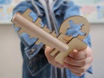 男孩在他的手上拿着一个木玩具 木钥匙和匙孔 免版税库存照片