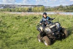 男孩在ATV旅行 免版税图库摄影