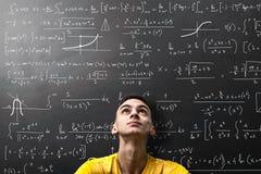 男孩注视着惶惑一个数学公式 库存照片
