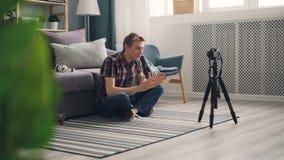 男性博客作者帅哥为网上vlog调整在然后记录录影的三脚架的照相机在家坐地板 股票视频