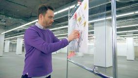 男性工程师与计划一起使用,设计设备 影视素材