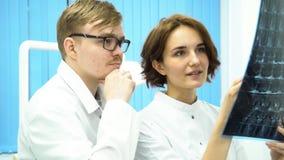 男性和女性医生谈论脑部扫描在医院 投入在玻璃和妇女的人指向射线照相 免版税库存照片