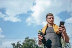 男性运动员,夏天运动场手智能手机,写消息互联网,应用程序脉冲锻炼活动 有效的生活方式 库存图片