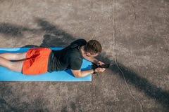 男性运动员,在运动场手智能手机的夏天,写消息互联网、应用脉冲和锻炼活动 库存照片