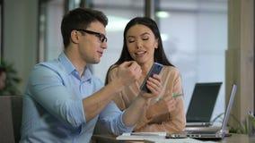 男性雇员陈列可爱的亚裔同事如何使用约会在电话的应用程序 股票视频