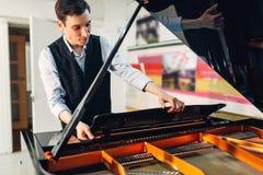 男性钢琴演奏家打开黑大平台钢琴盒盖  库存照片