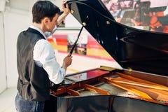 男性钢琴演奏家打开黑大平台钢琴盒盖  免版税库存图片