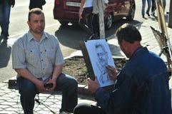 画在基辅街道上的人另一幅人讽刺画  免版税库存图片