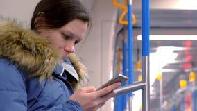 画象在一块空的地铁的疲乏的妇女乘驾和浏览在她的智能手机 侧视图 股票视频