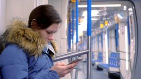 画象在一块空的地铁的疲乏的妇女乘驾和浏览在她的智能手机 侧视图 股票录像