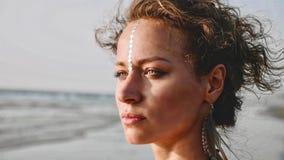 画象在海滩的年轻俏丽的妇女身分和看在海 免版税库存照片