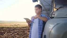 聪明种田 人农夫司机站立与一种数字片剂在卡车生活方式附近 慢动作录影 画象 股票视频