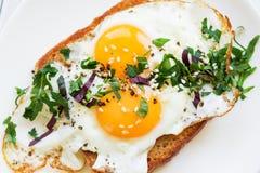 荷包蛋用在面包的两卵黄质与在一个白色盘的切好的绿色 库存照片