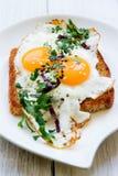 荷包蛋用在面包的两卵黄质与在一个白色盘的切好的绿色 免版税库存图片