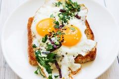 荷包蛋用在面包的两卵黄质与在一个白色盘的切好的绿色 库存图片
