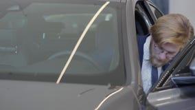 衣服和玻璃的确信的有胡子的人在后视镜打开在他的汽车的司机的门,坐里面并且看 股票录像