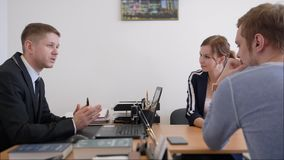 衣服的咨询年轻夫妇,微笑的投资经纪或者银行工作者做的友好的律师或财政顾问 股票录像