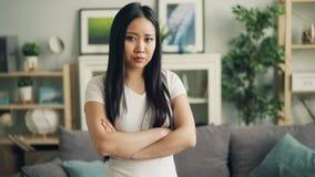 表现出生气亚裔的女孩画象看照相机,做哀伤的面孔和站立与胳膊的消极情感 股票录像