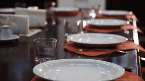 表设置在一家有名望的餐馆 干净和白色板材,玻璃觚在棕色餐巾和优美木 股票录像