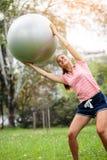 行使与pilates球的年轻女人在公园 拿着在她头和训练的瑜伽辅导员健身球 免版税库存图片