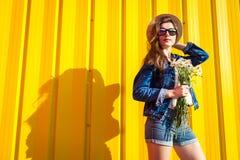行家女孩佩带的玻璃和帽子画象有花的反对黄色背景 夏天成套装备 方式 空间 免版税库存图片