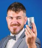 行家提议金钱蓝色背景关闭 概念低息贷款 富有的商人举行滚动了金钱 有胡子的人 免版税图库摄影
