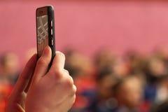 被弄脏的背景 报告文学照片或录影射击在一个手机 女孩举行智能手机在selfie方式或广播下 免版税库存图片