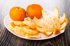 被剥皮的切片蜜桔,在盘的削皮的蜜桔在木桌上 免版税库存图片