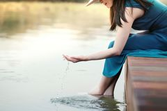 被拔去的生活或人的生活与自然概念 放松由河沿的愉快的年轻女人 微笑和坐甲板,接触 库存图片
