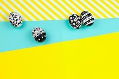 被洗染的黑白复活节彩蛋的汇集在黄色和蓝色背景的 免版税库存图片