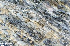 被碾压的石头 灰色黄色板岩特写镜头背景 免版税库存照片