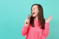 被编织的桃红色毛线衣的可爱的年轻女人有闭合的眼睛的在手中举行,唱在蓝色隔绝的话筒的歌曲 免版税库存照片