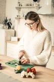 被编织的毛线衣的勤勉长发妇女使用烹调工具 免版税库存照片