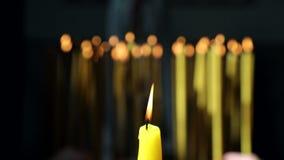 被点燃在教会里和在背景中一些个蜡烛的一个黄色蜡烛放了被投入的火给基督徒和 影视素材