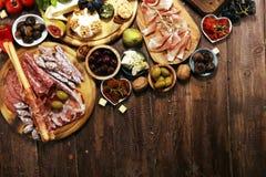 被设置的意大利开胃小菜酒快餐 乳酪品种、地中海橄榄、crudo、熏火腿二帕尔马,蒜味咸腊肠和酒在玻璃 免版税库存照片
