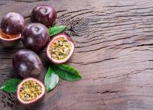 西番莲果和它的横断面用稀烂汁液充满种子 木背景 免版税库存照片