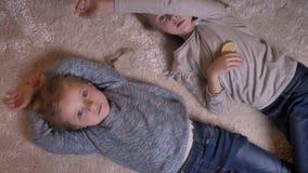 观看快乐入照相机的两个小滑稽的女孩顶面被射击的画象说谎在地板上 股票视频