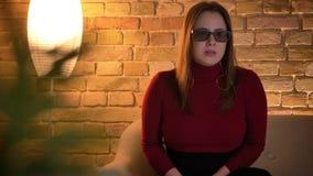 观看在电视的一3D恐怖电影和得到跃迁恐慌的年轻可爱的肥满女性特写镜头射击被吓唬 影视素材