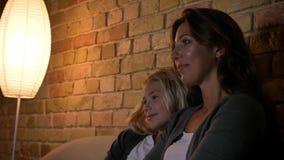 观看在电视的年轻白种人母亲和她的女儿特写镜头射击一部动画片笑和作出评论 股票录像