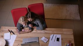观看在膝上型计算机的年轻白种人女性和她的小俏丽的女儿特写镜头顶视图一部动画片 股票视频