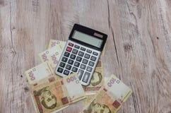 计算器和乌克兰hryvnia在木桌上 免版税库存照片